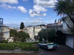 [Photo : Vue sur San Francisco du haut des collines avec voiture vintage]