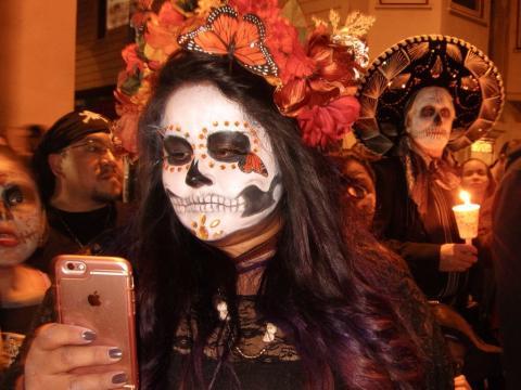 Jeune fille avec téléphone Apple et maquillage de Noche de los Muertos
