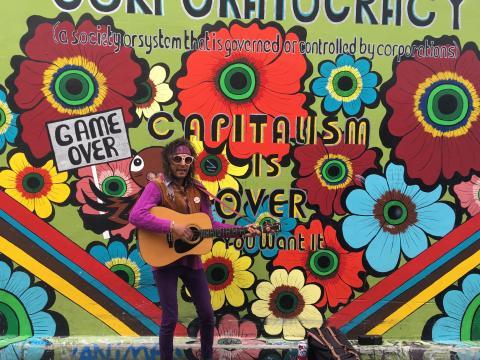 [Photo : guitariste hippie devant une fresque murale]