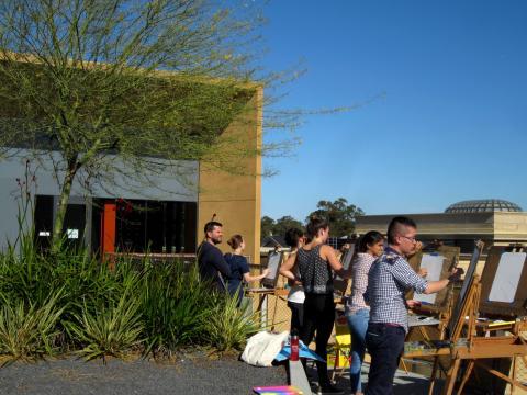 [Photo : Nouveau building à Stanford avec étudiants peignant]