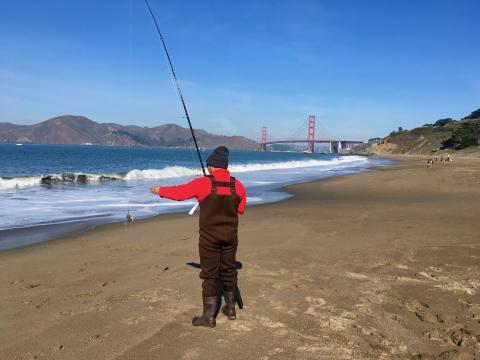 pêcheur sur une plage de San Francisco avec vue sur le pont