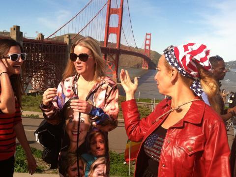 Jeune femmes devant le Golden Gate Bridge dont une avec un ensemble avec des portraits de Hillary Clinton