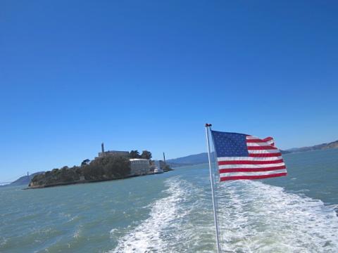Photo : trace d'un bateau avec drapeau américain et vue sur Alcatraz