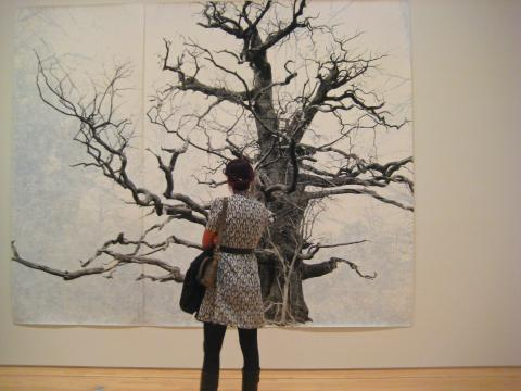 Photo : une dame devant le tableau d'un arbre en hiver